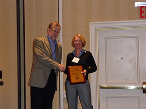 Elena Irwin (right) receiving a plaque from Vernon Henderson