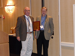 Jan Brueckner (left) receiving a plaque from Vernon Henderson