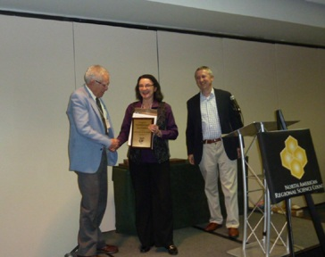 Janet Kohlhase (center) receiving a plaque from David Boyce and Gilles Duranton