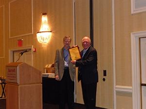 Richard Arnott (right) receiving a plaque from Vernon Henderson